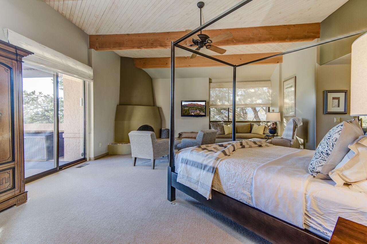 Queen Bed, Sitting Area with a Gas Fireplace, Walk-in Closet, and Patio Access