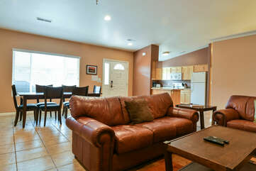 Sofas, Coffee Table, Dining Set, and the Kitchen with Refrigerator.
