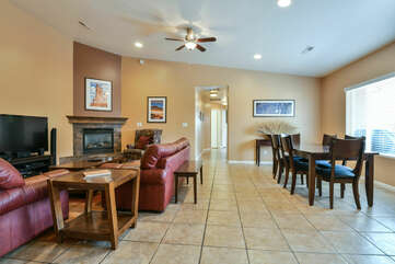 Fireplace, Sofas, Coffee Table, TV, Ceiling Fan, and Dining Set.