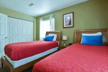 Bedroom with Two Beds, Nightstands, and Closet Doors.