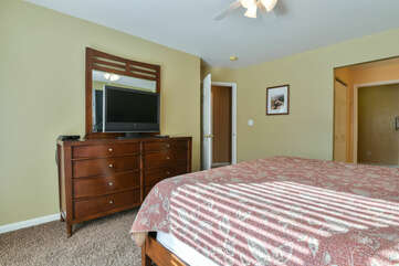 Drawer Dresser, TV, Large Bed and Ceiling Fan.