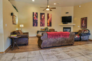 Arm Chair, Sofas, Ceiling Fan, Fireplace, and TV.
