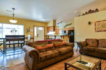 Sofas, Dining Table, Chairs, Front Door, and Kitchen with Bar and Stools.
