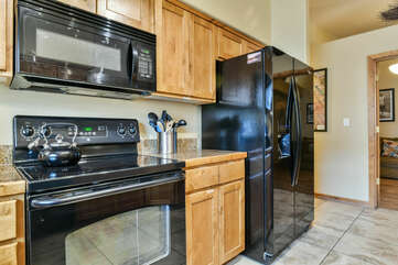 Refrigerator, Microwave, Stove, and Kitchen Cabinets.