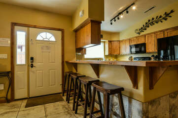 Kitchen Bar, Stools, Front Door, Refrigerator, and Microwave.
