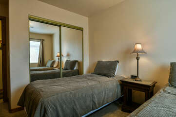 Mirror Closet Doors, Two Beds, Nightstand, and Table Lamp.