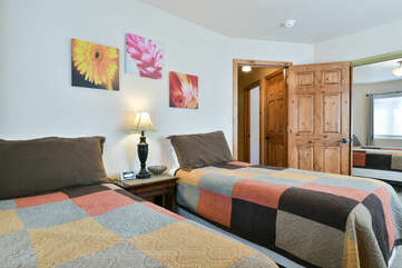 Two Beds, Nightstand, Table Lamp, and Mirror Closet Door.