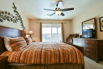 Bedroom with Large Bed, Ceiling Fan, Dresser, and TV.