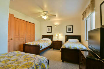 bedroom with three twin beds and a TV