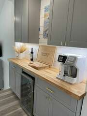 A butcher block counter top highlights the beverage center with coffee station and wine refrigerator.