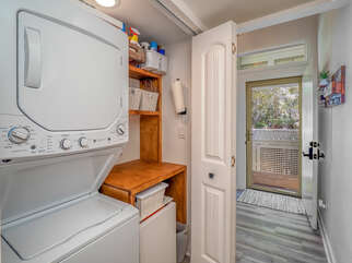 The laundry closet has a stacked washer and dryer. A folding table is convenient for the laundry duties.