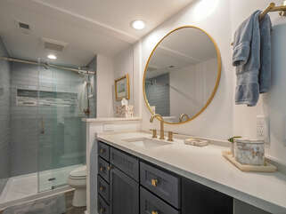 The master bath is stylish with tiled walk-in shower and quartz counters.