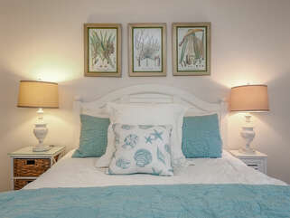 A new queen size bed with beautiful bedding.