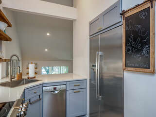 Stainless steel appliances, white quartz counters, and ship lap showcase the beautiful light gray custom cabinetry.