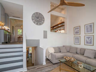 x Up a few steps lands you in the living room with soaring ceiling and sunroom with amazing views.