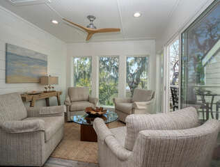 Relax and enjoy the views from this sunroom with deck access.