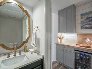 Powder room on the upper level with adjoining beverage center.