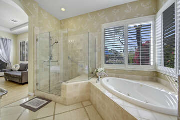 Private, en suite bathroom features a jacuzzi tub, tile shower, and his and hers vanity sinks.