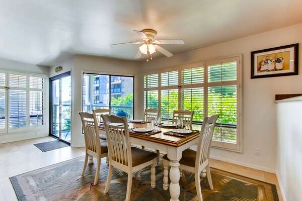 Dining table for 6 with overhead light and fan, bright windows with adjustable blinds and entrance onto covered patio