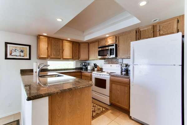Open kitchen with granite countertops and recessed lighting