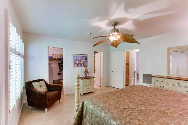 Master bedroom with king size bed, ceiling fan and overhead light, dresser and drawer space and walk-in closet