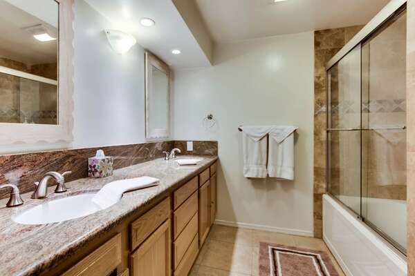 Master bathroom with large dual vanity, recessed light, shower/tub combo, toilet and ample cabinet and drawer space