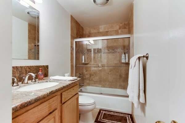 Guest bathroom with a shower/tub combo, large vanity, toilet and cabinet and drawer space