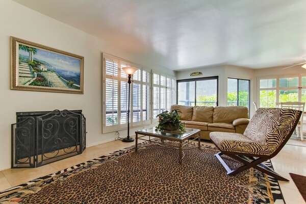 Living room with comfortable seating, gas fireplace and plenty of natural light