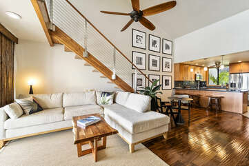 Living Area with Loft Staircase, Cream Colored Sectional and Views of the Kitchen