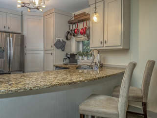 A breakfast bar with two barstools are available.