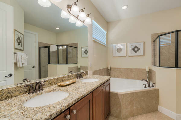 Ensuite bathroom featuring garden tub and shower