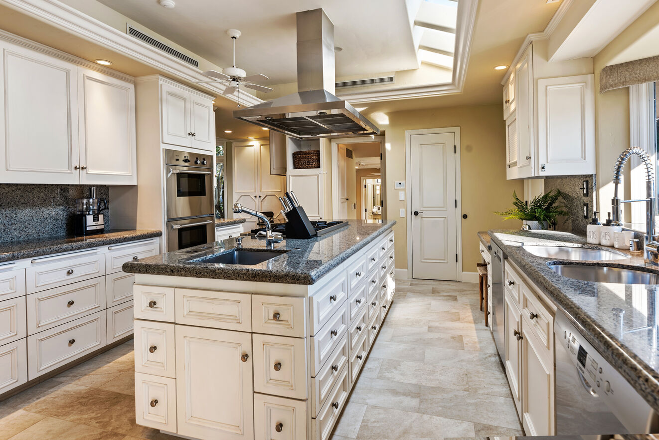 The chef's kitchen with ample counterspace, professional grade stainless steel appliances, and custom cabinetry.