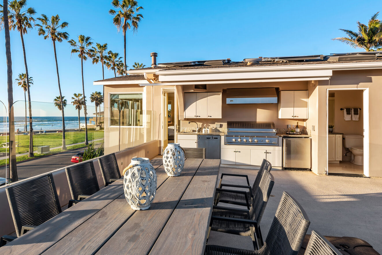Rooftop dining table, outdoor kitchen, and half bath.