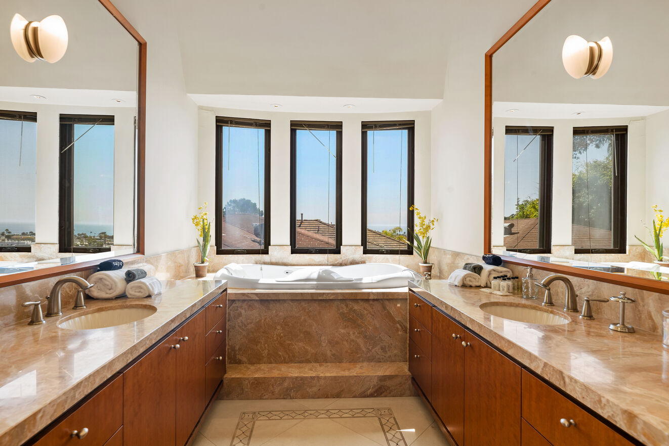 Master bathroom with her and hers vanities,, tub and shower