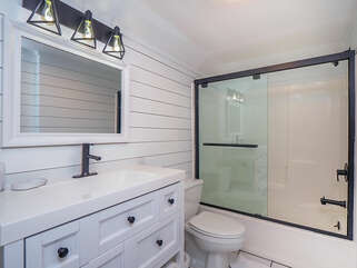 The remodeled en-suite bath has ship lap, new vanity and tub/shower combo.