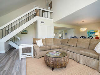 The great room is open to the dining area. A large sectional couch and beautiful golf course views.