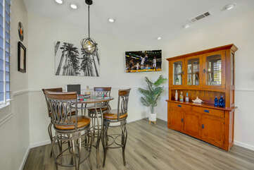 Have a cocktail at the game room table with four bar height chairs.