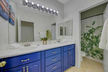 The hallway bathroom is located across from bedroom 3 and features a bathtub and shower combo and two vanity sinks.