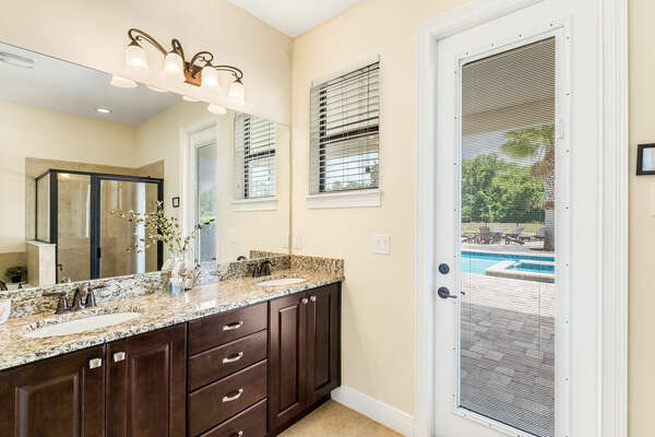 En-suite bathroom has a walk-in shower and a door with access to the pool