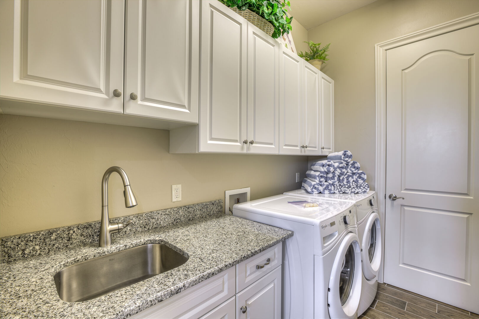 Laundry room with sink and washer/dryer in our Fort Myers vacation home rental
