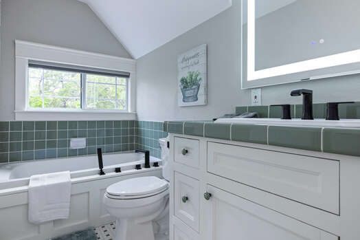 Upper level full shared bathroom with a soaking tub and handheld shower head, and lighted mirror
