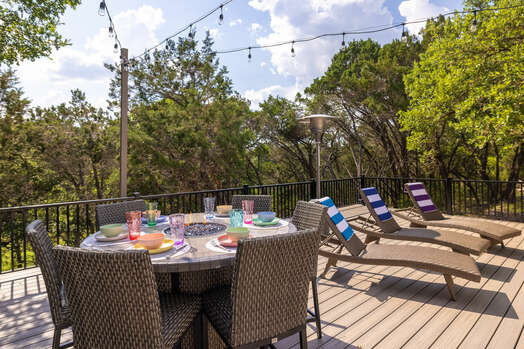 Sky deck has lounge chairs, space heaters, and 6-seat high boy table with fire ring