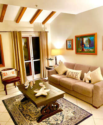 Living room with beach decor, queen sofa bed, ceiling with high beams, doors to balcony