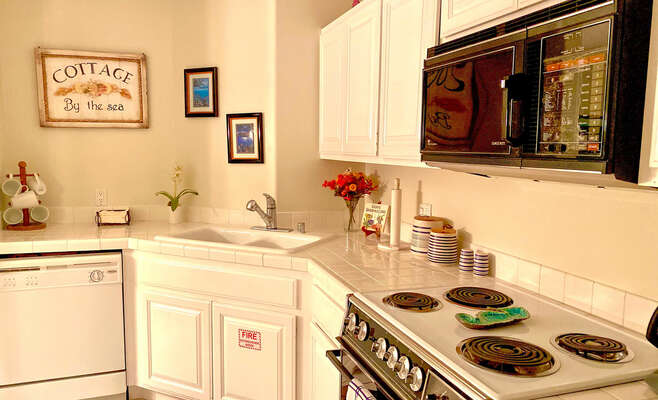 Kitchen with oven, sink, microwave, dishwasher, coffee maker, and refrigerator