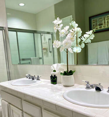 Bathroom with dual vanity sinks, mirror, toilet, and shower/ tub combination
