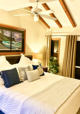 Master bedroom with king size bed, high beam ceiling with fan, doors to private balcony, TV, and lamps