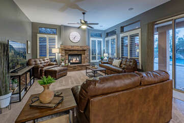 Great room has comfortable seating, a large TV and views of the backyard oasis. The fireplace is for decoration only.