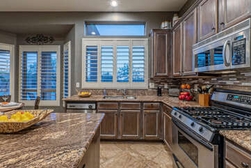 The modern kitchen has an island and ample counter space for preparing and serving a feast.