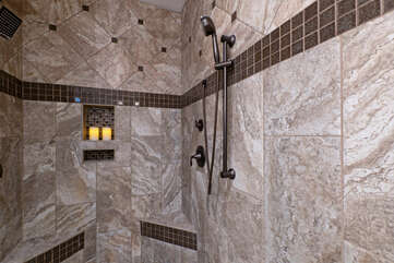 The walk-in shower in the primary bath is beautifully remodeled.