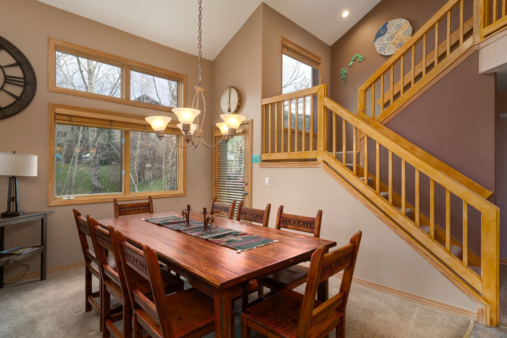 Door to the deck and hot tub behind the spacious dining table. Stairs to the upper level 2 bedrooms with loft overlooking the living space.